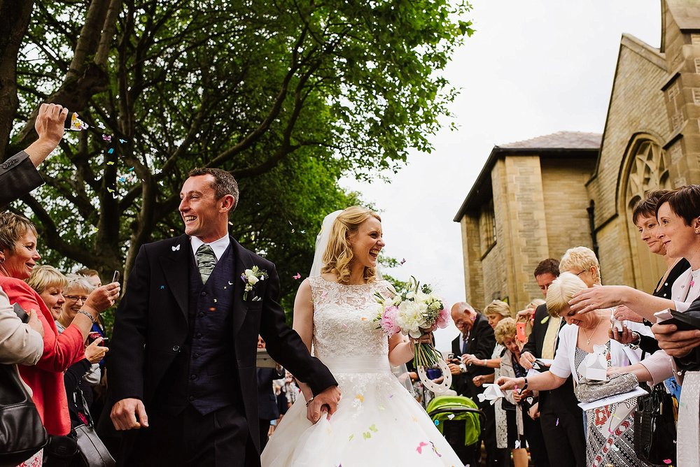 The bride and groom leaving the church grounds whilst they are lined up on either side by all their guests who are throwing confetti on them