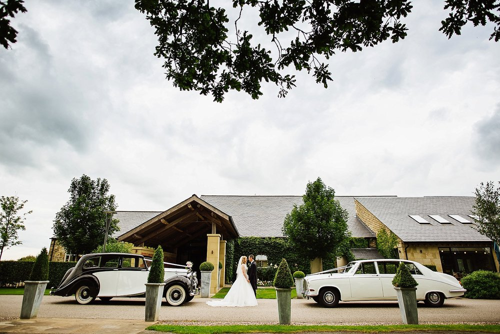 Wedding portrait of the Bride and Groom with their two cars outside Stanley House