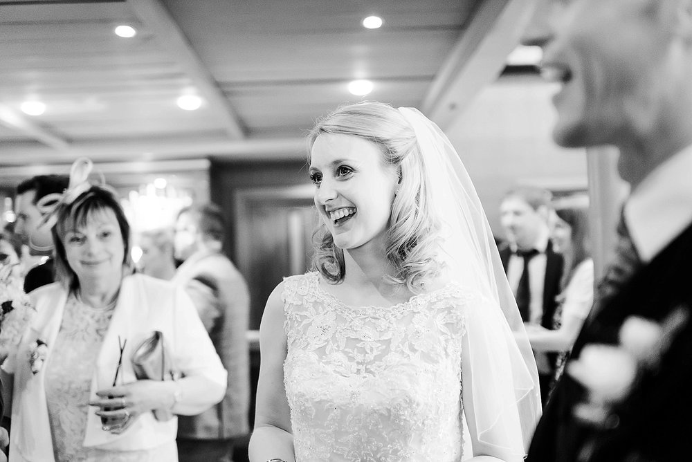 A beautiful portrait of the bride smiling with the groom in the foreground whilst guest look on