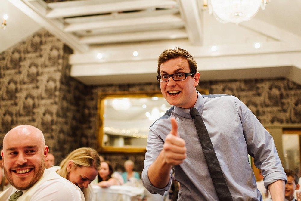 man looking at camera and giving thumbs up