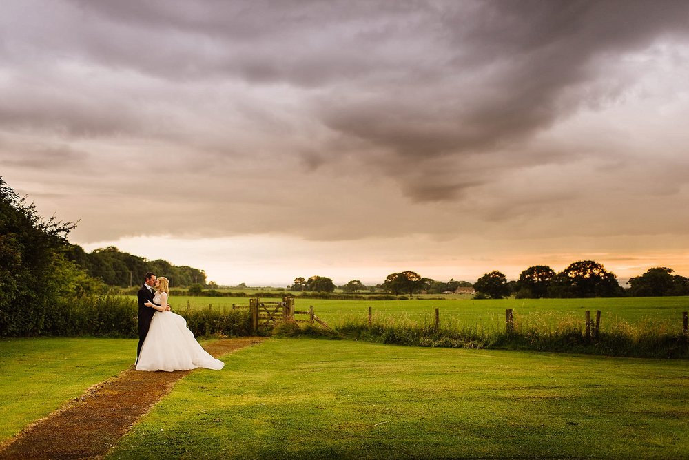 Portrait of the bride and groom at Stanley House with a cloudy sunset
