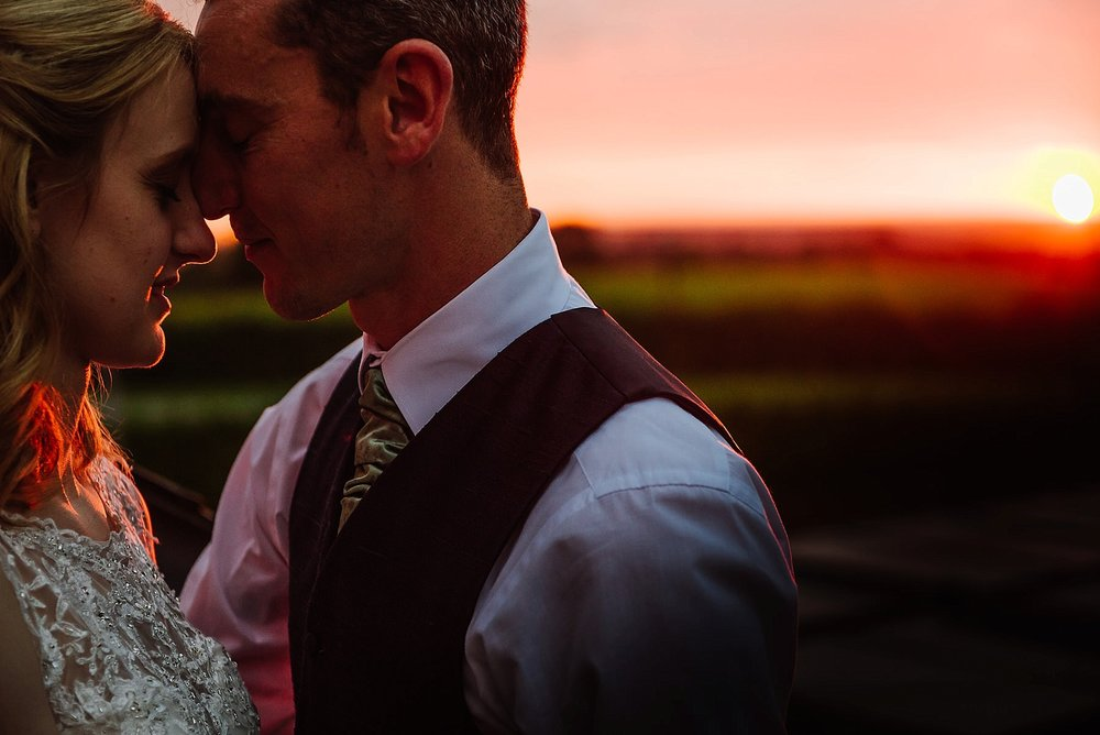Wedding photograph of the married couple with the sun setting behind them