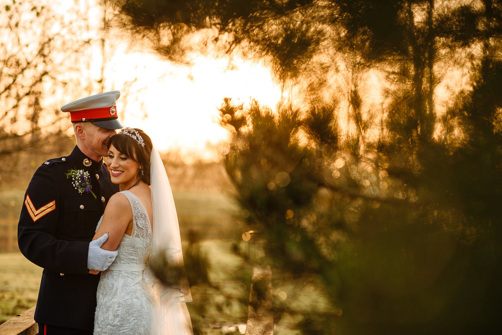 Military groom cuddling his bride at Charnock Farm near Leyland at sunset