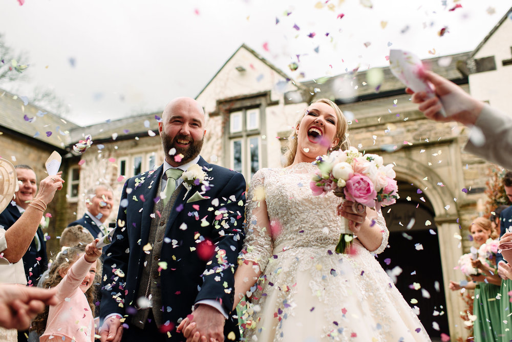 Lauren & Rick outside Mitton Hall, covered in confetti on their Lancashire wedding day