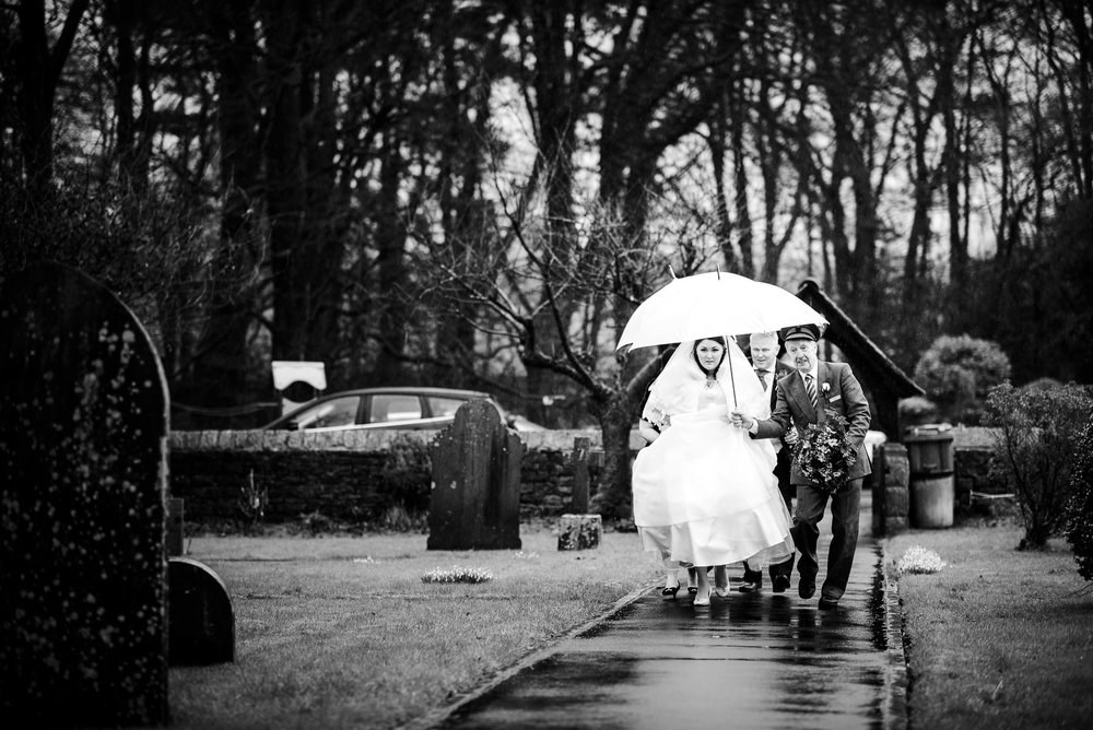Donna walking towards the church on a rainy english wedding day