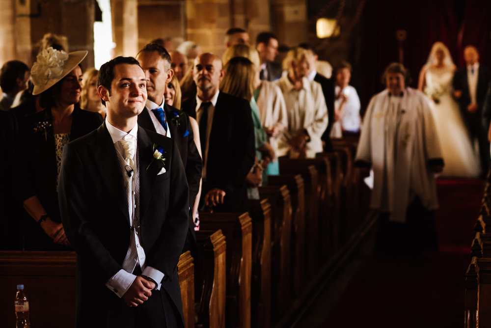 An anxious groom waits for his bride in the church