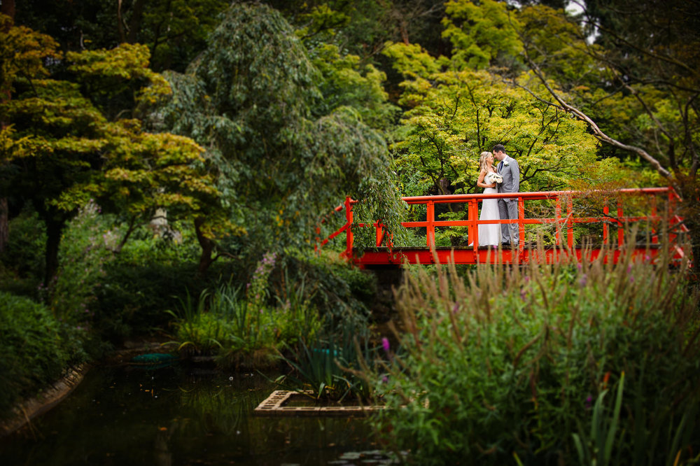 Sarah and Dan on a bridge at the lake of fanhams hall hotel hertfordshire