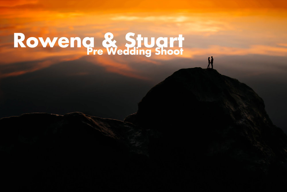 Couple stood on top of a mountain at sunset
