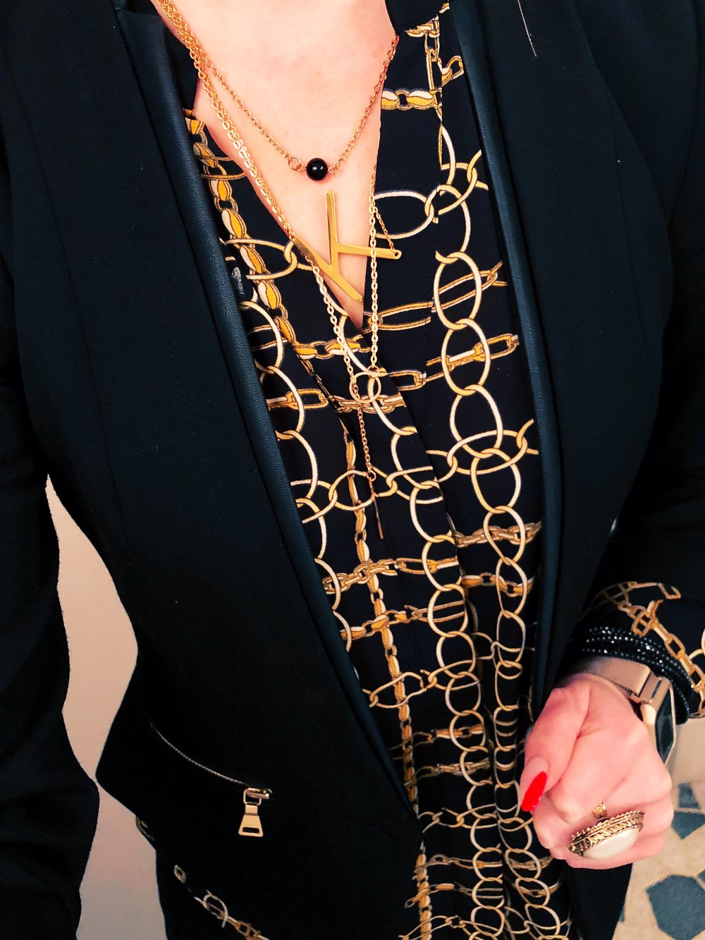 Up close on the layered necklace choices with a classic blouse and blazer at work.