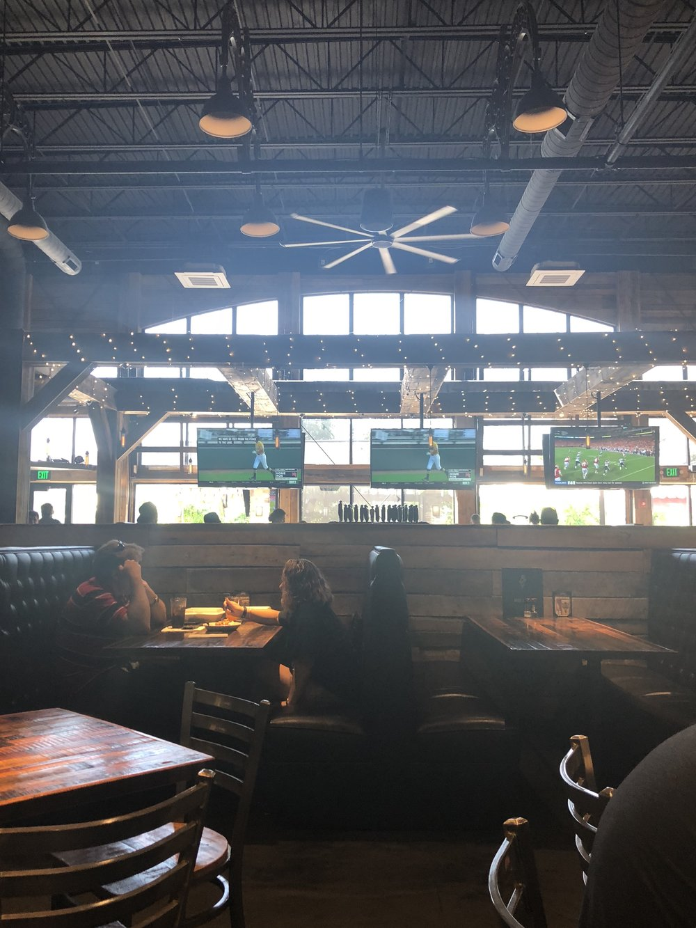 Large Bar area with plenty of TVs looking into the outdoor patio