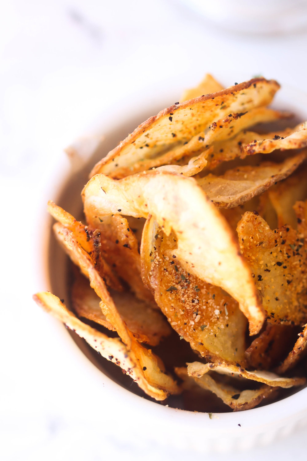 Crispy Baked Potato Chips are a healthier alternative to store-bought potato chips. They take 30 minutes or less and you can easily customize your spices.