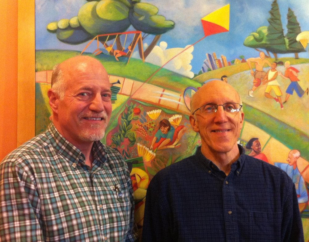 Pictured: Dan Nordley (left) with creative director John Seymour-Anderson in TPC's Baker Building offices. The painting by Janice Perry Porter shows the firm's roots in the Seward neighborhood, overlooking Triangle Park.