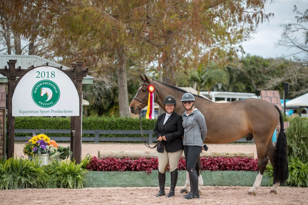 "Michelle Durpetti and Cassius, pictured with Caitlyn Shiels (right), accepting the 3'3"" Amateur-Owner 36 and Over Hunter reserve championship during week two of the 2018 Winter Equestrian Festival. Photo by Jump Media"