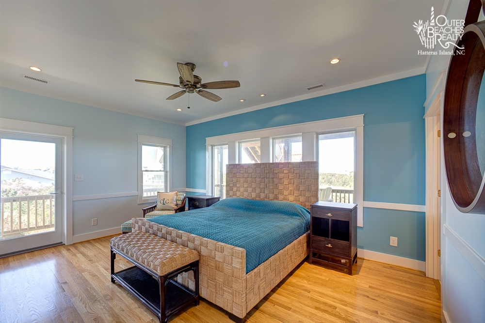 CALM - Situated on the second level, this master bedroom contains a king-size bed and private bathroom, nestled right in the flow, with easy access to the green backyard and ocean view in front.