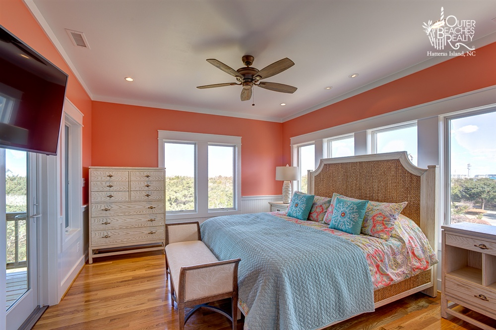 COURAGE - Situated on the second level, this master bedroom contains a king-size bed and private bathroom, overlooking the natural landscape surrounding the home.