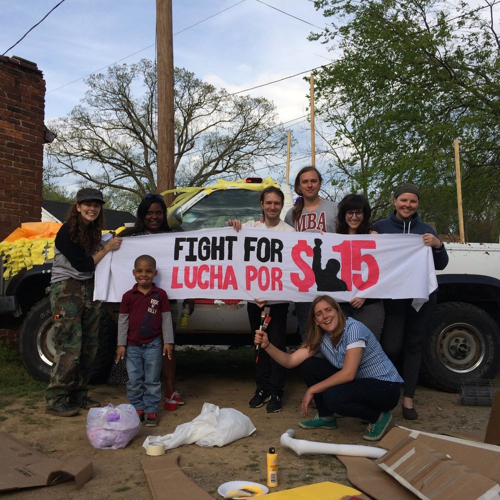 Jessi with fellow activists preparing puppets, banners, and a decorated float for an economic justice protest in 2016.