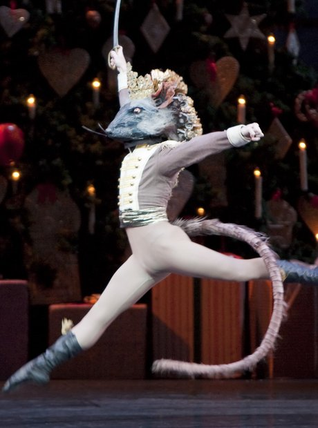 A ballet dancer playing the role The Mouse King from  The Nutcracker  performing a move known as a arabesque