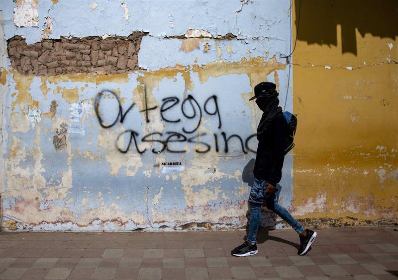 """Un joven con la cara tapada camina frente a una pintada durante la marcha """"Nicaragua Unida Jamás Será Vencida""""."""