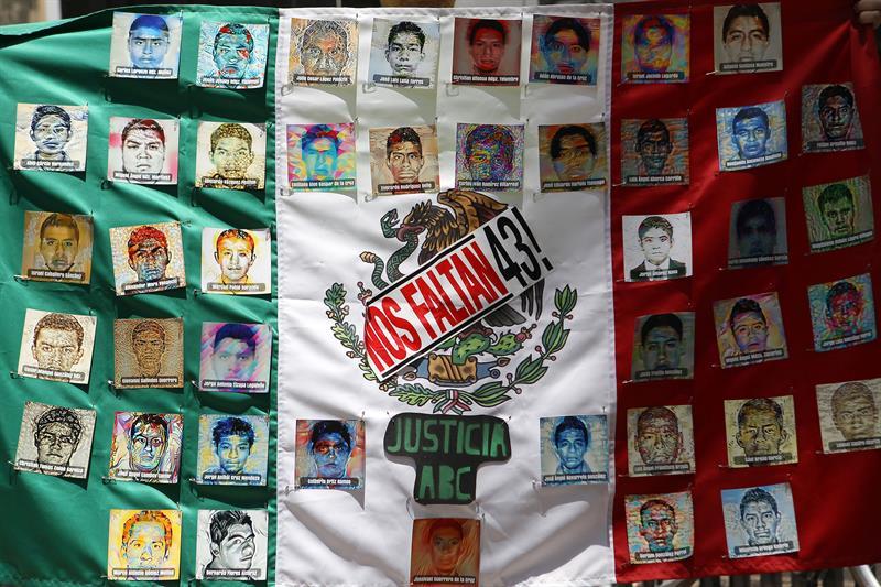 Fotografía de una bandera de México con imágenes de los 43 estudiantes desaparecidos de las Escuela Normal Rural de Ayotzinapa.