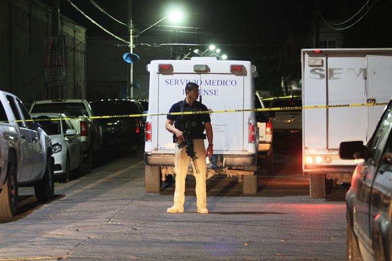 Fotografía de archivo del 22 de marzo de 2018 que muestra a un policía custodiando el sitio donde unas ocho personas resultaron muertas y otras 11 heridas, tras un ataque de un grupo armado en el municipio de Purísima del Rincón, en el estado de Guanajuato (México