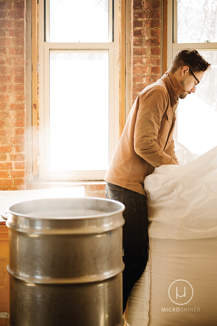 a worker at Kings County Distillery prepares grain for the mash