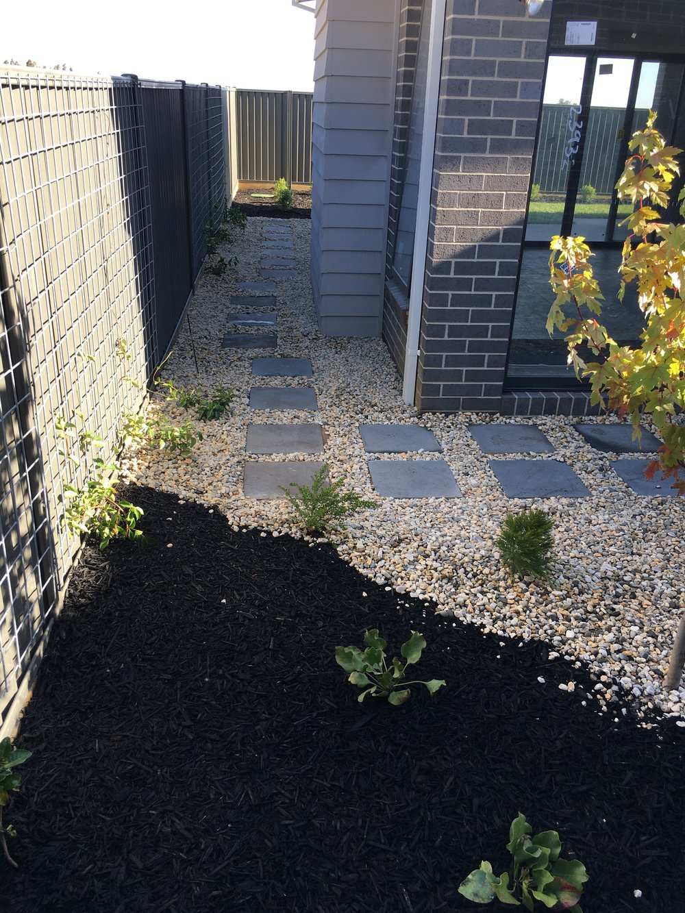 Garden bed with black mulch and pebble mulch with stepping pavers