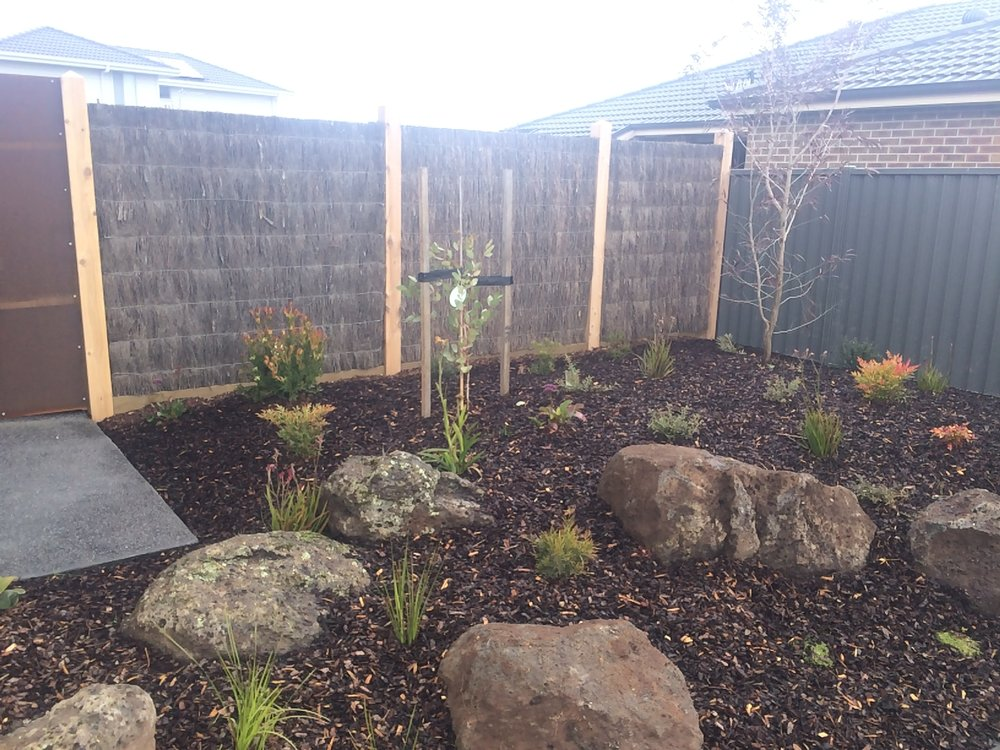 Garden bed with rocks and brush panel fencing