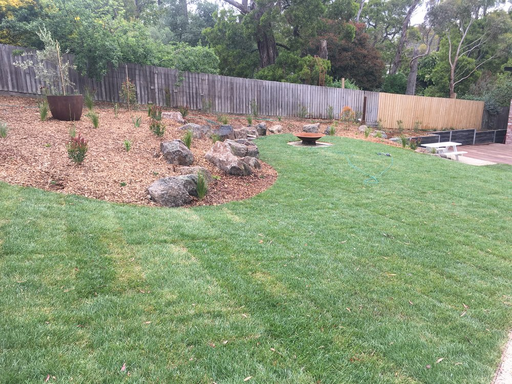 Instant turf, mulched garden beds with scattered rocks and firepit