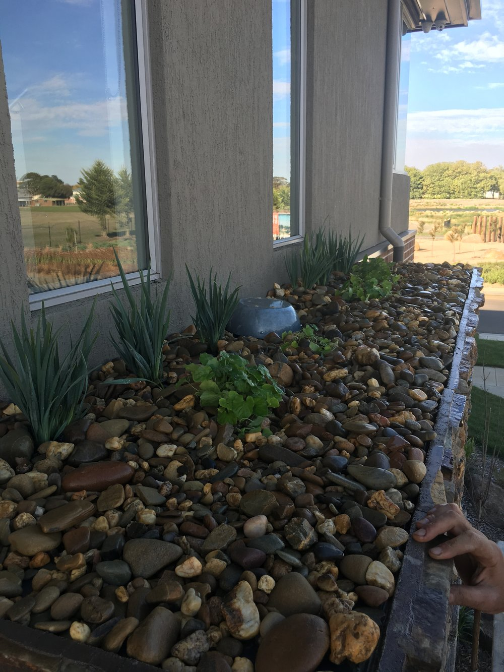Raised garden bed with pebble mulch and stack stone face