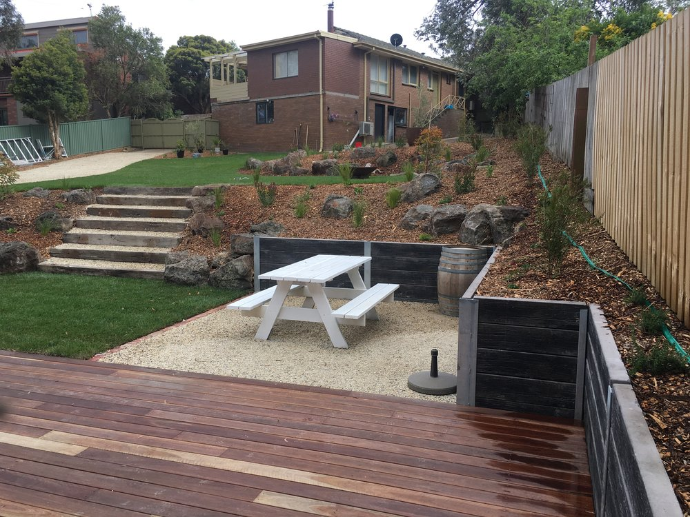 Retaining wall, deck, steps, garden beds with scattered rocks, instant turf and lilydale toppings pad