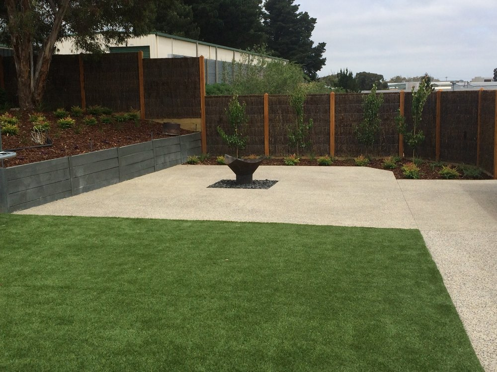 Synthetic turf, retaining wall with garden bed, exposed aggregate, fire pit and brush panel fencing with exposed posts