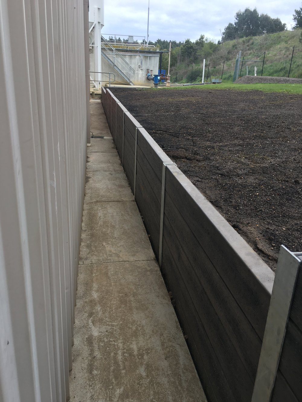 Woodgrain-look concrete sleeper retaining wall with steel posts
