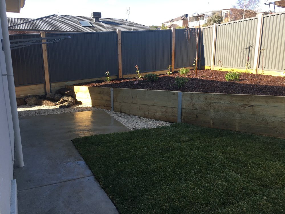 Instant turf, sleeper retaining wall with garden bed, rock area and pebbles