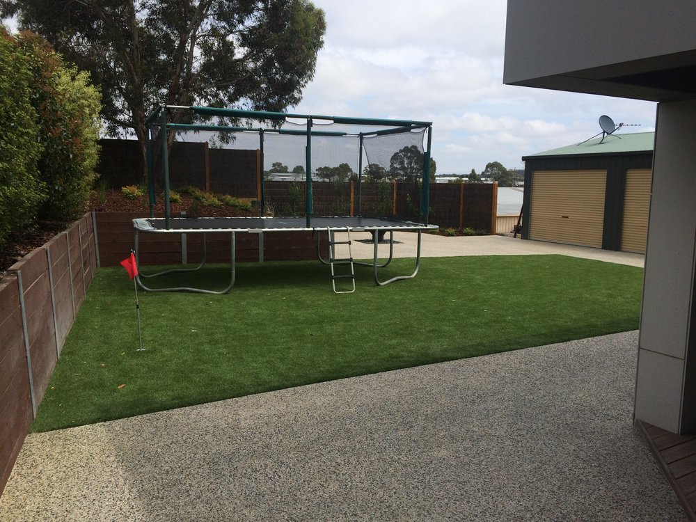 Synthetic turf, retaining wall with garden bed, exposed aggregate, fire pit and golf hole