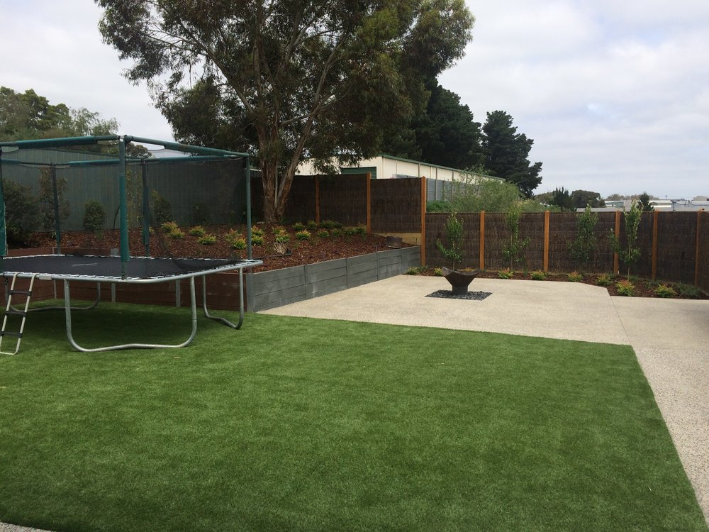 Synthetic turf, retaining wall with garden bed, exposed aggregrate, firepit and brush panel fencing with exposed posts 2.JPG