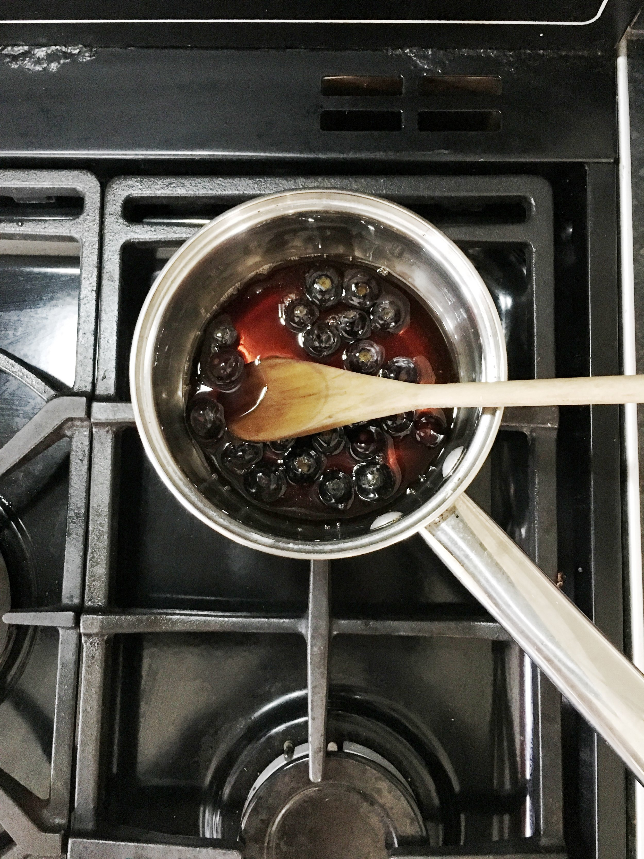 Blueberries and maple syrup in a pan. Heat gently and simmer to make blueberry syrup