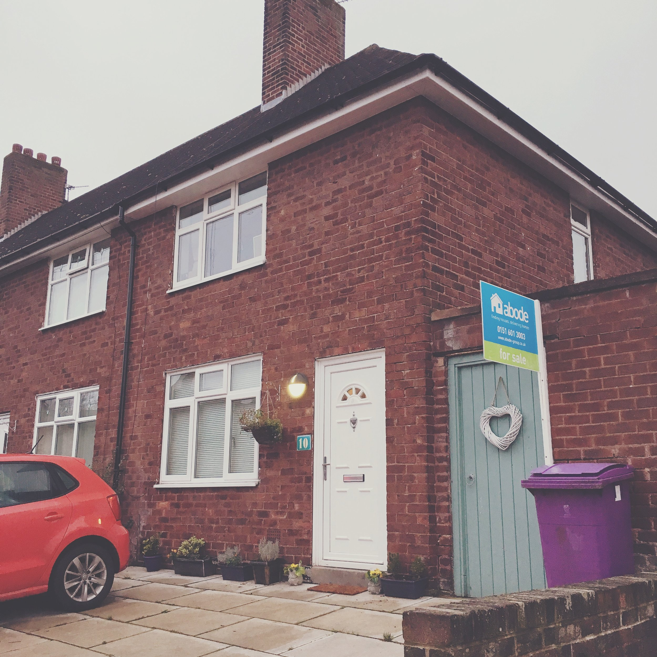 Small two up two down terraced house with for sale sign outside. Duck egg blue door with white wicker heart