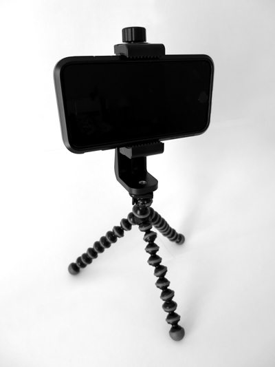 I recently got this tool to use my iPhone for recording videos and pictures during my daily work more properly. It's composed of two products: A cell phone tripod adapter and a flexible portable tripod. - You can find on Amazon the best shopping options depending on your country.