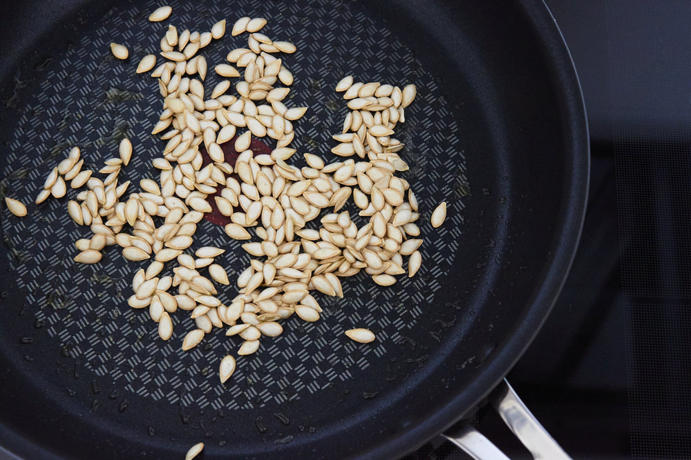 How to Roast Pumpkin Seeds - seeds at the beginning of roasting, with olive oil and salt | In Carina's Kitchen