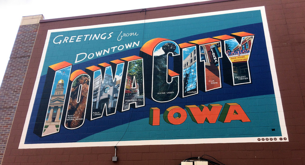 Greetings from Downtown Iowa City mural, a commission for the Iowa City Downtown District on the Iowa City Public Library. Based off a Curt-Teich large letter postcard, the mural features institutions of the arts in Iowa City. Completed over the course of 7 days in May of 2017. Approximately 16'x24'.