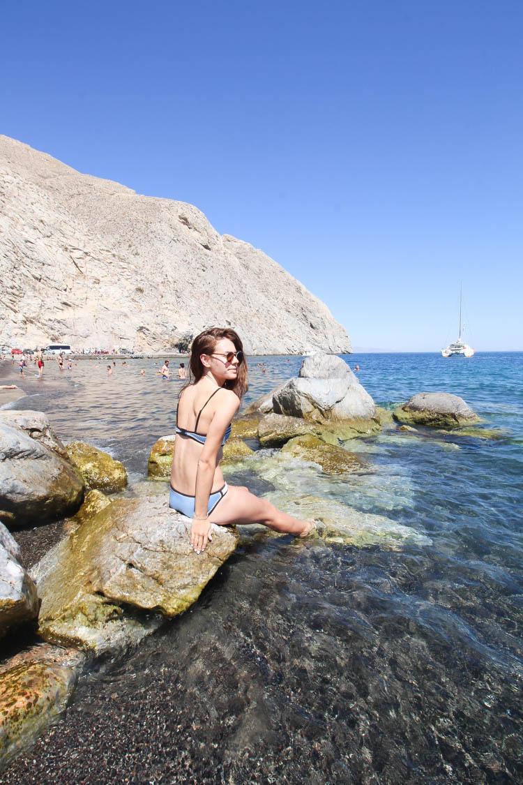 Bikini at black sandy beach Santorini