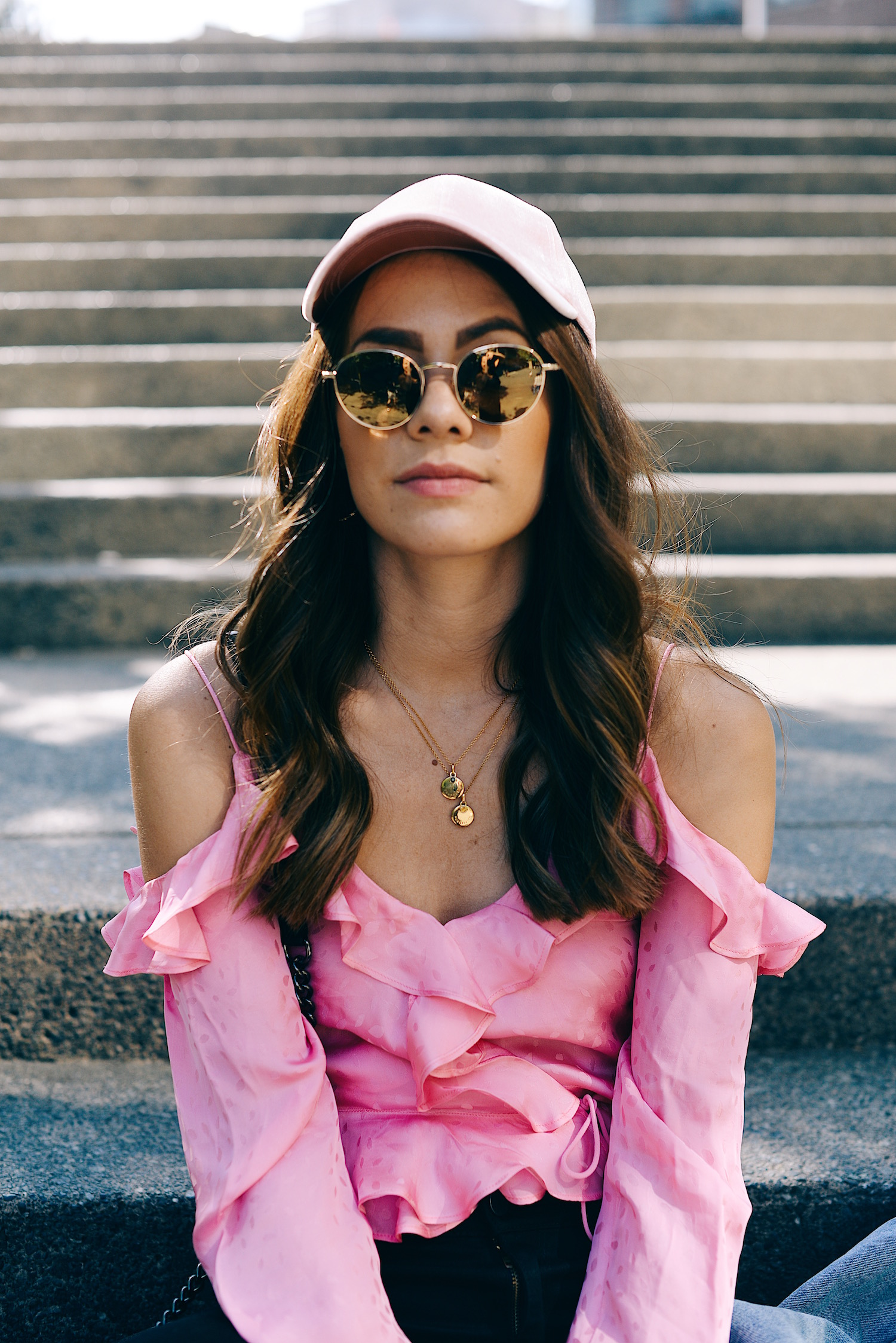 Pink shirt with Mejuri necklaces and pink cap