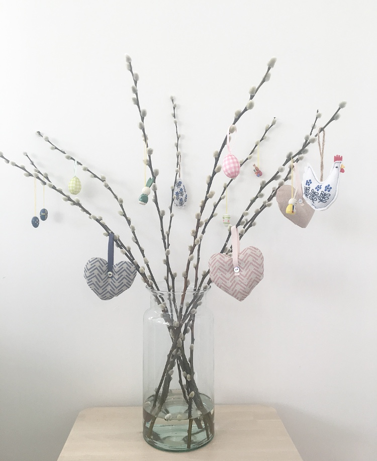 Create An Easter Tree - An Easter tree has become a popular way to decorate your home in time for Easter. It can make the perfect centre piece to a dining table or a side table. As a starting point all you need is a bundle of twigs, blossom branches or a bunch of Pussy Willow. Purchase a few pastel coloured decorations to hang from the branches, we have added a selection of our new lavender filled Linen Hanging Hearts too! You could even add some arrangements around the base of your vase - maybe some candles or mini chocolate eggs in a bowl!The vase we have used - Broadwell Recycled Glass Vase- Tall