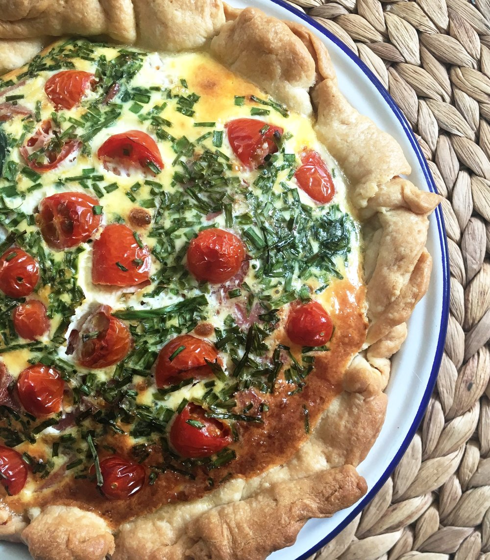 Spinach, Feta & Tomato Quiche - Meat alternative: Add chopped pancetta or chorizoIngredients100g creme fraiche3 large eggs2 handfuls of spinach1 handful of plum tomatoes1 small bunch of chives100g feta cheese1 garlic clove1 short crust pastry sheet (recipe below, but shop bought will save you time!)MethodShort Crust Pastry:1. Sift 225g plain flour into a large bowl, add 100g diced butter at room temperature and rub in with your fingertips until the mixture resembles fine breadcrumbs.2. Stir in a pinch of salt, then add 2-3 tbsp water and mix to a firm dough. Knead the dough briefly and gently on a floured surface. Wrap in cling film and chill for 15mins. Roll out and place in a flan tray or like us keep it rustic in an enamel dish.Filling:1. Crumble the feta on the bottom of the short crust pastry.2. Pour olive oil into the saucepan and when it's heated, throw in the spinach and cook until wilted. Once wilted, place evenly on top of the feta and pastry.3. Beat eggs, garlic and creme fraiche together. Pour over the top of the spinach.4. Sprinkle a handful of cut chives onto the quiche and add chopped plum tomatoes.5. Place in 180ºC oven, gas mark 4 and cook for 45mins until lightly set.