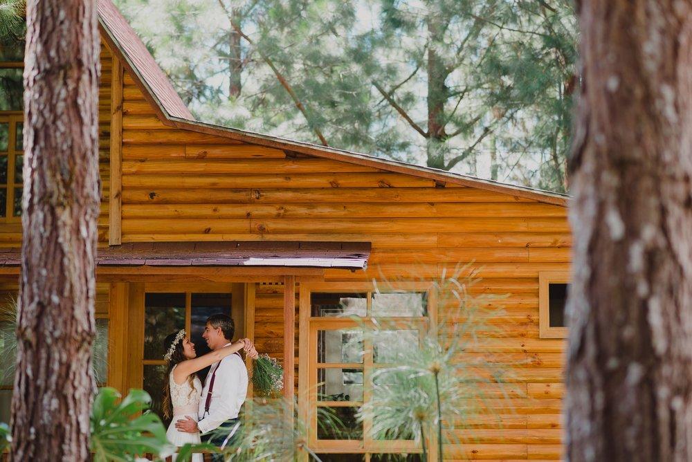 abrazo de pareja de novios frente a su cabaña