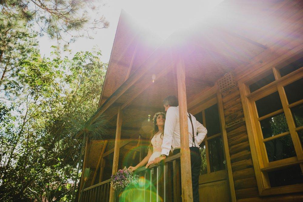novios recien casados frente a su cabaña