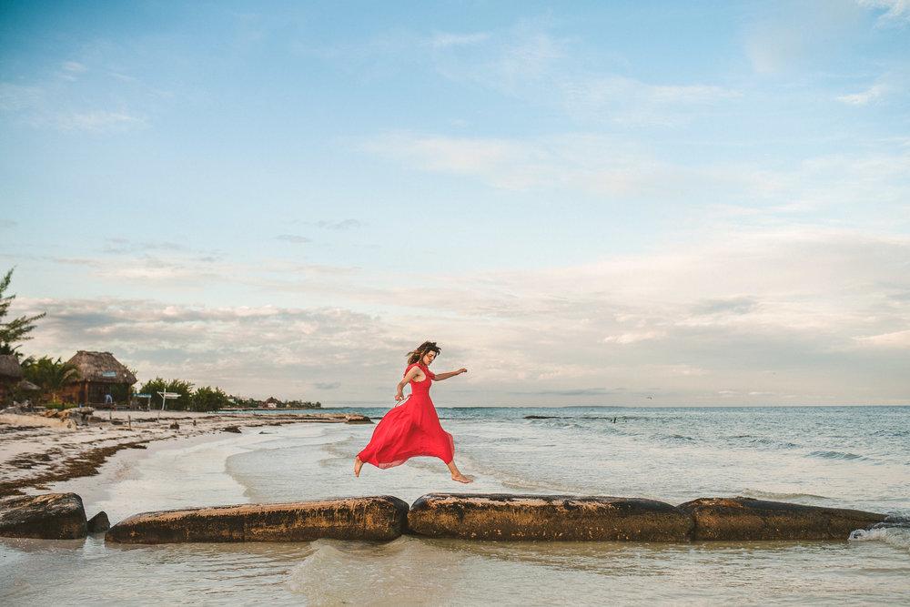 mujer con vestido rojo saltando por la playita