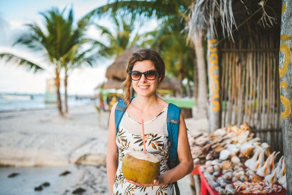 mujer tomando un coco en holbox