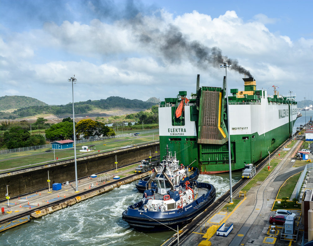 Tugboat helping push a ship through the locks towards Gatun Lake