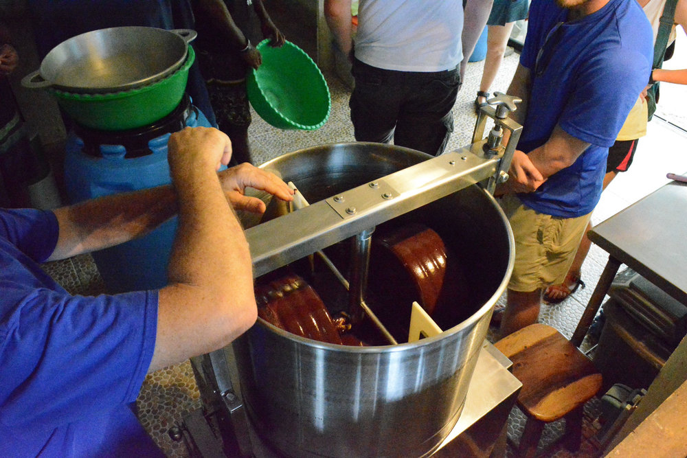 Explaining the process of tempering. They use a bowl over another bowl of ice to cool down the chocolate liquid